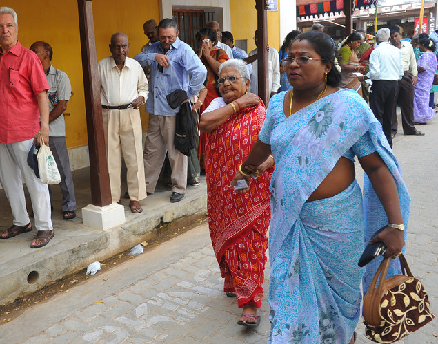 An elderly Indo-French citizen (C) is escorted to a polling both by an assistant in Pondicherry on April 22, 2012, before casting her vote during the first round of French presidential elections.