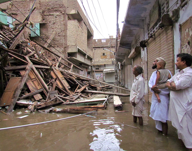 Pakistani residents look at a collapsed house caused by torrential rain.