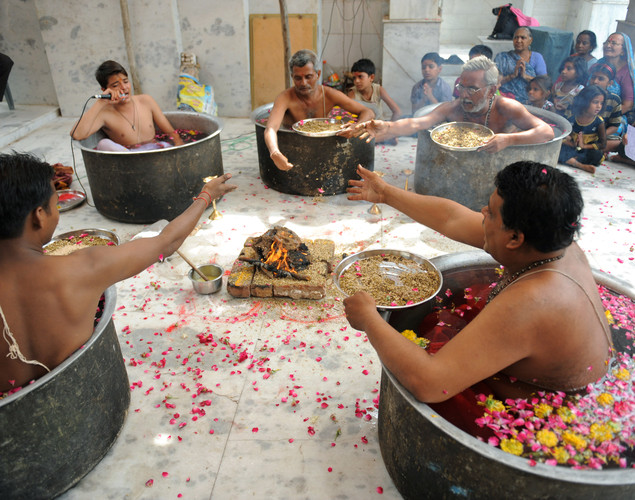 They sit inside huge pots filled with water and flower petals to perform the ritual.