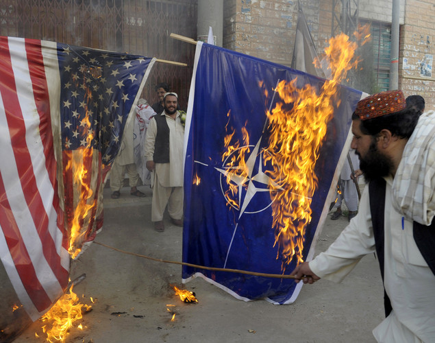 Activists of Awami Majlis-e-Amal Pakistan burn NATO and US flags during a protest in Quetta to denounce the resumption of NATO supplies into Afghanistan.