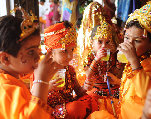 Indian children dressed as Hindu God Lord Krishna sip cold drinks after celebrating pre-Janamashtmi festivities at a police camp in Amritsar on August 9,2012, on the eve of the 'Janmashtami' festival.