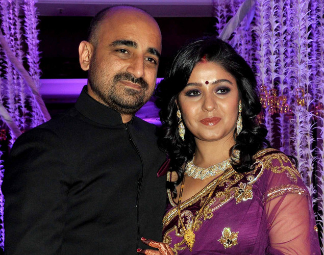 Bollywood playback singer Sunidhi Chauhan (R) poses with her husband musician Hitesh Sonik during their wedding reception in Mumbai.