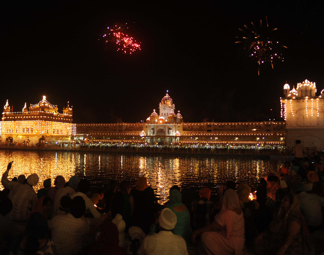 Indian Sikh devotees watch a fireworks display over the illuminated Golden Temple in Amritsar.