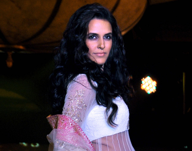 Neha Dhupia displays a creation by designer Manish Malhotra for a public awareness campaign Save and Empower the Girl Child in Mumbai.
