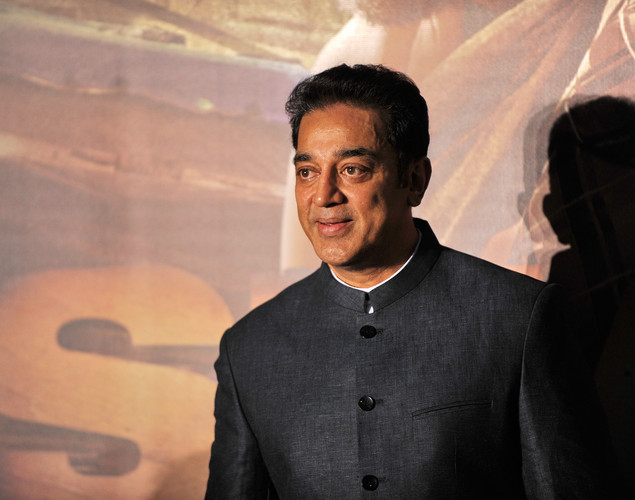 Indian actor Kamal Haasan poses for the media after arriving at the green carpet to attend the premier of the new movie 'Shanghai' during the International Indian Film Academy (IIFA) awards event, in Singapore.