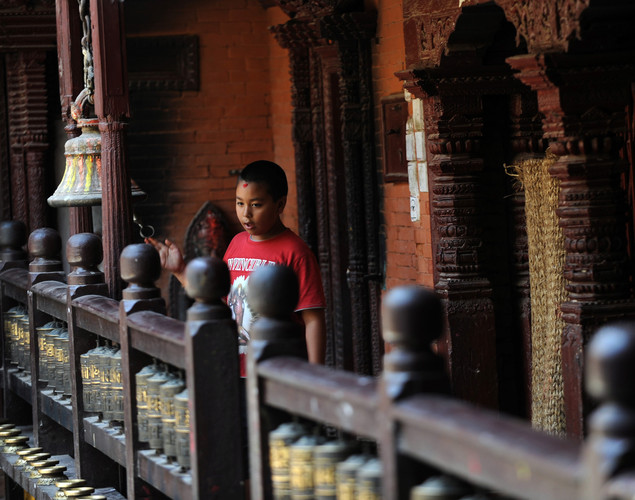 A Nepalese boy rings a bell at the Golden temple near Patan durbar square in Lalitpur on August 3, 2011. The Golden Temple was founded during the 12th Century near Patan Durbar Square, a UNESCO World Heritage Site,famous for fine ancient art, making of metallic and stone carving statues.