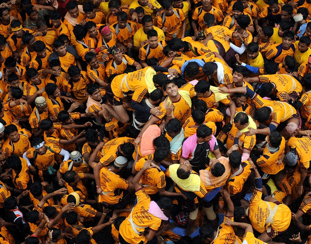 Indian Hindu devotees form a human pyramid to break the dahi-handi, curd-pot, suspended in the air during celebrations of Janmashtami, which marks the birth of Hindu God Lord Krishna, Mumbai on August 10, 2012.