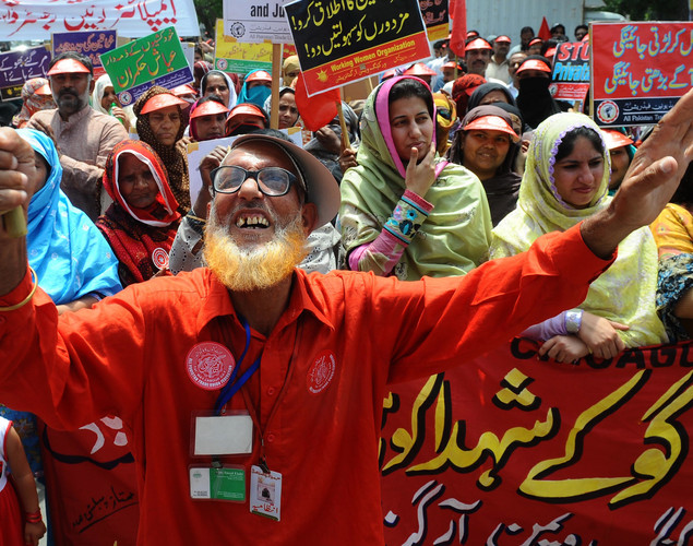 Pakistani labor union workers carry placards as they shout slogans during a May Day rally in Lahore.