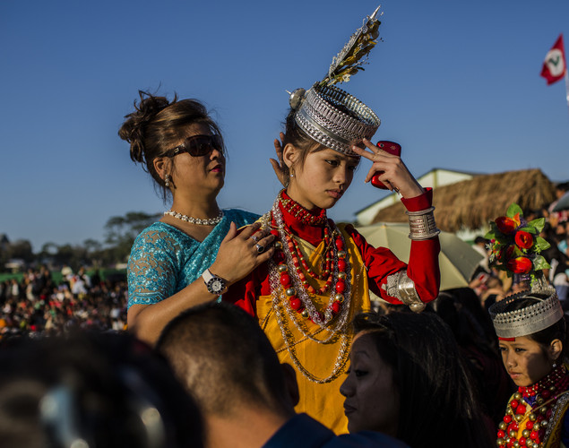 A mother prepares her daughter, dressed as a tribal Khasi maiden in traditional costume, ahead of participating in the traditional dance during the Shad Suk Mynsiem Festival.