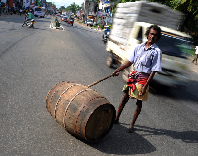 A toddy tapper wheels a barrel down a street containing coconut tree sap to make palm wine, or toddy as it is locally known, in Wadduwa.