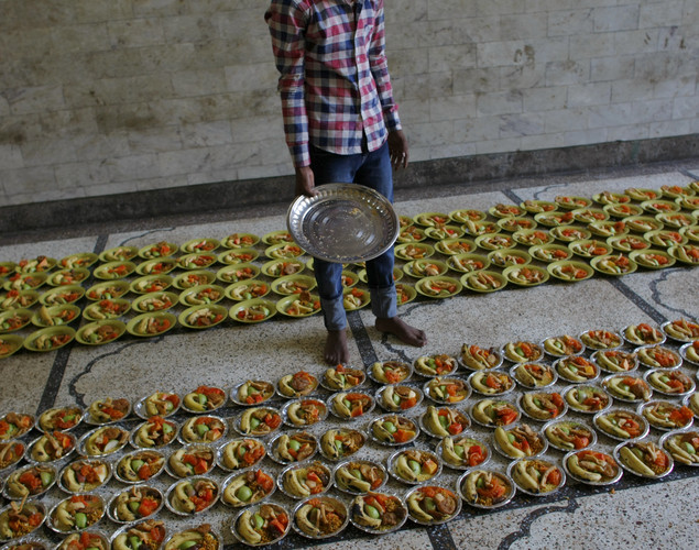 Muslim volunteers lay out communal food as they prepare to break their fast on the first day of the holy month of Ramadan at the shrine of 13th century Sufi Muslim saint Hazrat Nizamuddin Aulia in New Delhi.