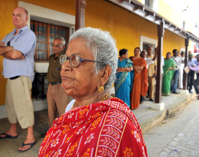 An elderly Indo-French citizen (C) walks to a polling booth in Pondicherry on April 22, 2012, before casting her vote during the first round of French presidential elections.