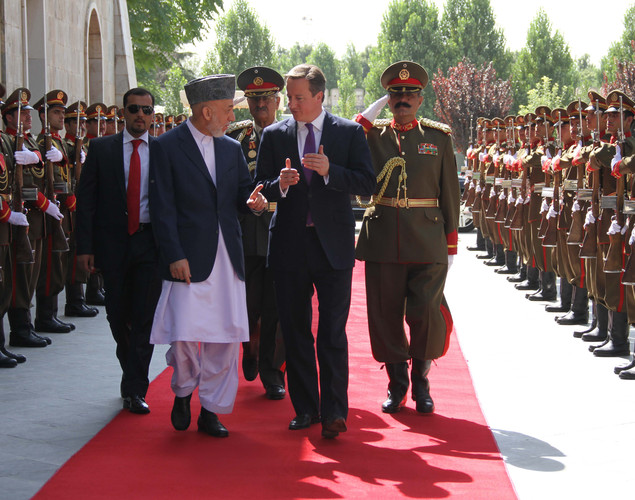 Afghan President Hamid Karzai (2L) speaks with Britain's Prime Minister David Cameron (2R) as they walk past a guard of honour ceremony in Kabul.