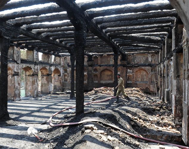 A firefighter clears debris inside the charred remains of the 200-year old shrine of Sheikh Abdul Qadir Jeelani, also known as Dastigheer Sahib, in downtown Srinagar.