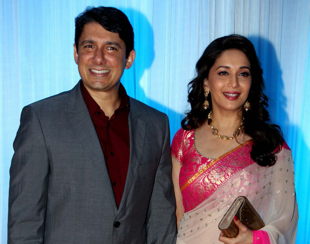 Bollywood film actress Madhuri Dixit (L) and her husband Sriram Nene pose during the wedding reception of film actress Esha Deol and husband Bharat Takhtani in Mumbai.