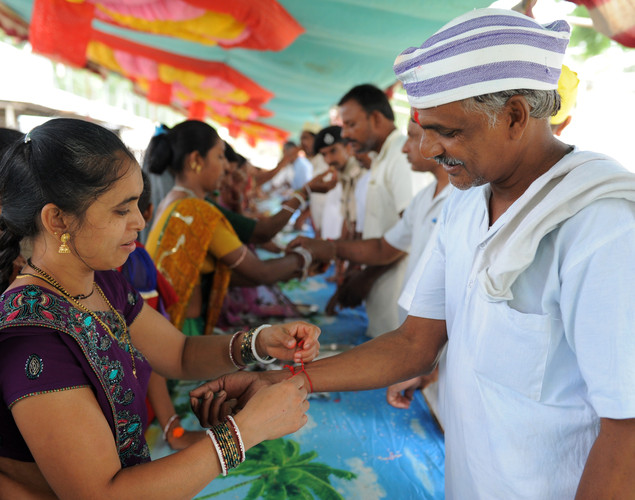 An Indian inmate of the Sabarmati Central Jail (R) looks on as his sister ties a rakhi bracelet to his wrist during the Raksha Bandhan festival in Ahmedabad.