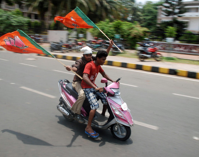 India's opposition Bharatiya Janata Party (BJP) activists wave party flags and shout slogans as they ride a scooter during a protest in Bhubaneswar on May 31, 2012, part of a nationwide strike against a rise in petrol prices by nearly 11.5 percent.