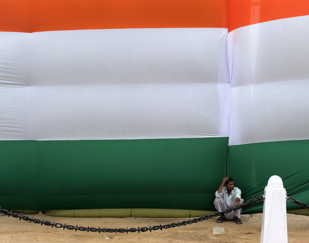 An Indian man sits in the shade of a huge Indian flag adorning the India Gate monument in New Delhi during Independence day celebrations on August 15, 2012.
