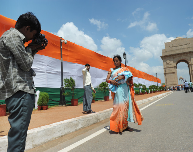 An Indian woman has her photo taken by a street photographer at the India Gate monument in New Delhi during Independence day celebrations on August 15, 2012.