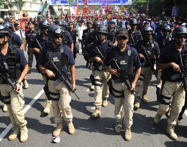 "Members of the Bangladeshi Special Weapons And Tactics (SWAT) security force stand guard in front of a rally in celebration of the Bengali New Year or ""Pohela Boishakh"" in Dhaka."