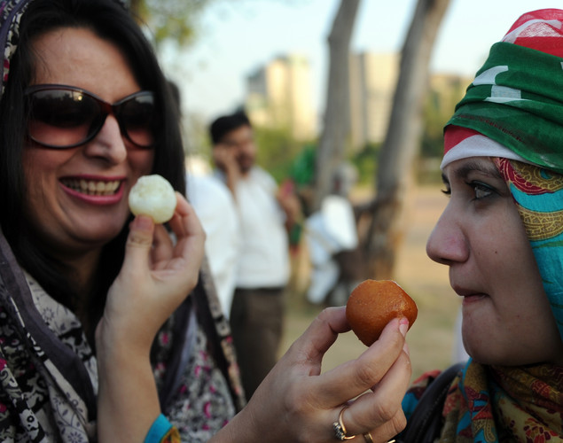 Supporters of Pakistani cricketer turned politician Imran Khan of Pakistan Tehreek-i-Insaaf (PTI - Movement for Justice) eat sweets while they celebrate following the verdict against Pakistani Prime Minister Yousuf Raza Gilani in Islamabad.