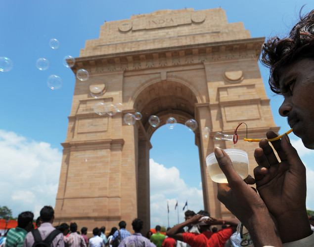 A street vendor blows soap bubbles at the India Gate monument in New Delhi on August 15, 2012.