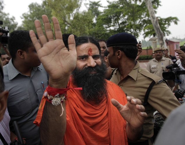 Indian yoga guru Baba Ramdev waves to the media as he leaves after paying homage at Rajghat, the memorial to late Mahatma Gandhi, before relaunching his anti-corruption protest in New Delhi, India.