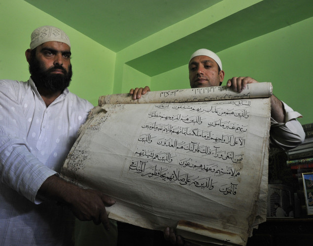 Syed Khalid Hussain (R), chief custodian of the 200-year old shrine of Sheikh Abdul Qadir Jeelani - also known as Dastigheer Sahib - which was engulfed in flames on June 25, displays a rescued handwritten copy of the Koran, claimed to once been in the posession of Abu Bakr, a companion of Islam's Prophet Muhammad, in Srinagar.