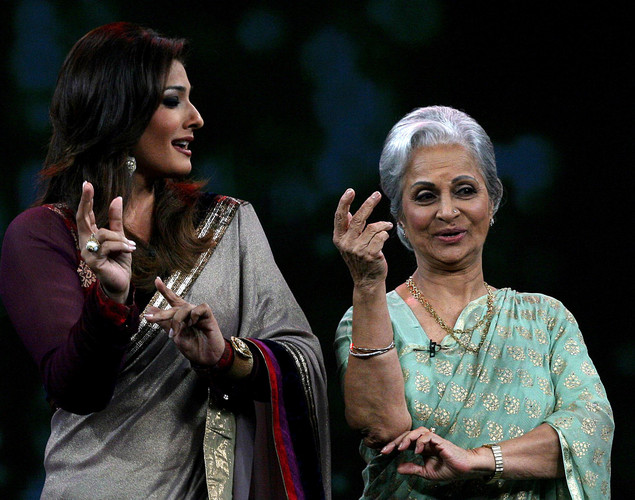 Waheeda Rehman (R) and show host Raveena Tandon perform onstage during the NDTV talk show 'Issi Ka Naam Zindagi' in Mumbai on April 19, 2012.