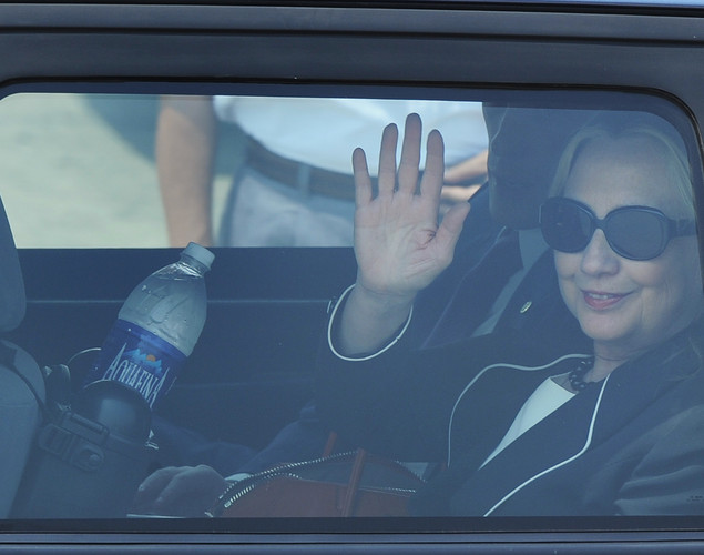 US Secretary of State Hillary Clinton waves from inside a vehicle following her arrival at the Netaji Subhash Chandra Bose International Airport in Kolkata.