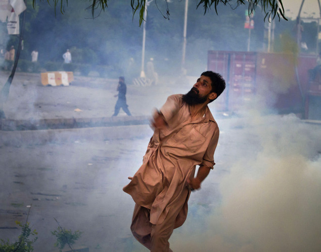 A Pakistani protester hurls back a tear gas canister fired by police, not pictured, during clashes that erupted as protestors tried to approach the U.S. embassy, in Islamabad.
