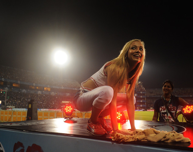 A Deccan Chargers cheerleader clears water off their platform as the IPL Twenty20 cricket match between Deccan Chargers and Kolkata Knight Riders is delayed due to rain at The Barabati Stadium.