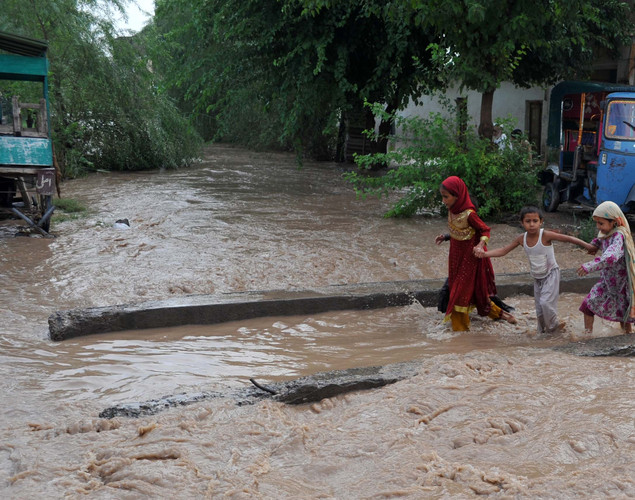 Pakistani children cross a flooded area of Peshawar.