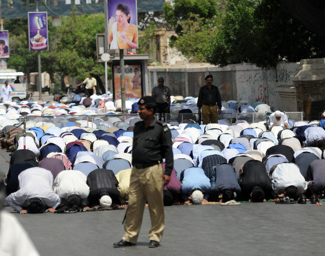 Pakistani policemen stand guard as Muslim devotees offer Jummat-ul-Vida, last Friday, prayers on a street during the holy month of Ramadan in Karachi.