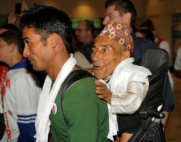 Chandra Bahadur Dangi, the 72-year-old Nepali crowned the 'world's shortest man' by Guinness World Records is carried as he arrives at Sydney International Airport for a week of promotional engagements.