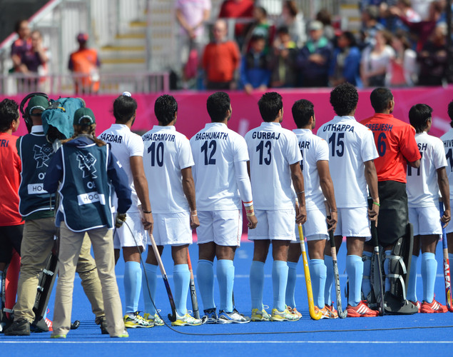 India's hockey players listen to their national anthem before the start of the preliminary round men's field hockey match of the London 2012 Olympic Games between The Netherlands and India at the Riverbank Arena in London on July 30, 2012.