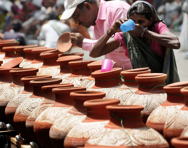 A woman drinks water stored in clay pots on the streets of New Delhi.