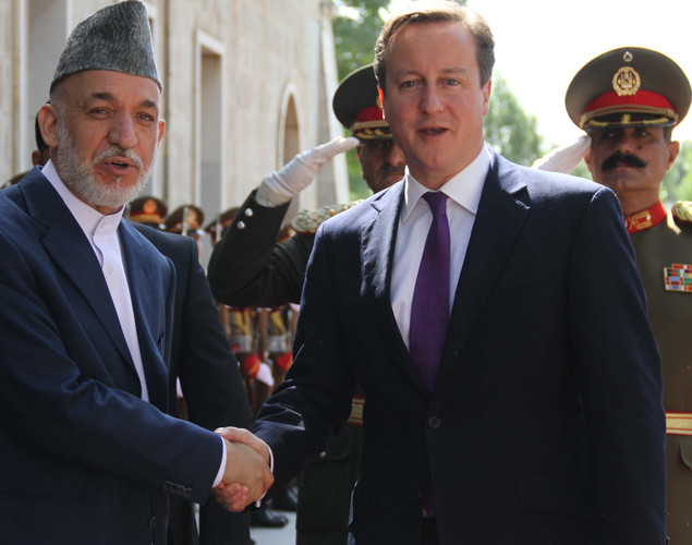Afghan President Hamid Karzai (L) shakes hands with Britain's Prime Minister David Cameron (2R) after inspecting a guard of honor ceremony in Kabul.