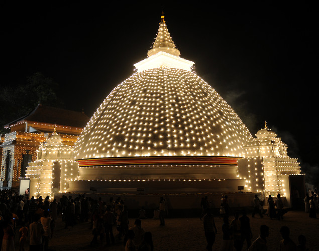 Sri Lankan Buddhist devotees gather around an illuminated temple in Kelaniya during the annual Buddhist festival of Vesak.