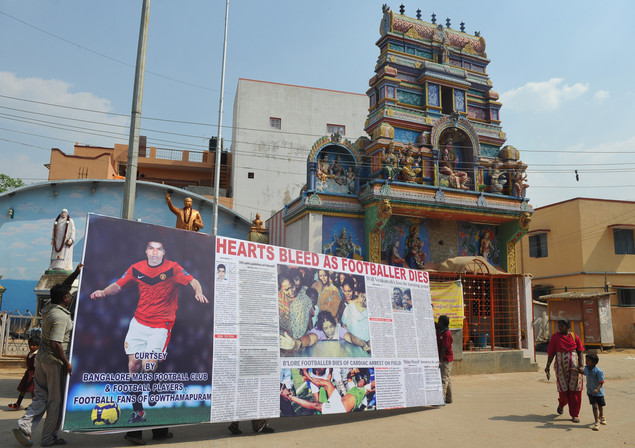 Pedestrians walk past a poster paying homage to 27 year old Indian professional footballer D. Venkatesh in Bangalore on March 22, 2012, the day after his death.