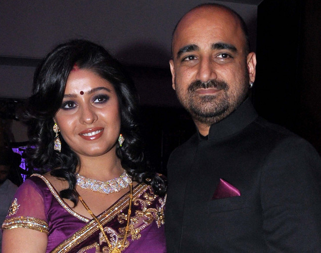Bollywood playback singer Sunidhi Chauhan (L) poses with her husband musician Hitesh Sonik during their wedding reception in Mumbai.