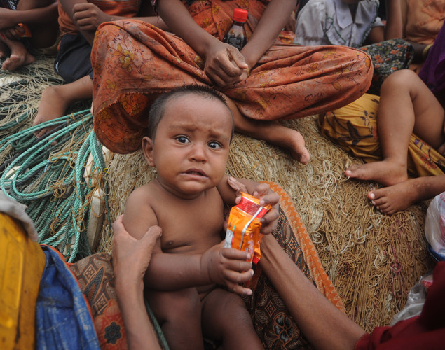 A Rohingya Muslim toddler, fleeing sectarian violence in Myanmar, is pictured on an intercepted boat while trying to cross the Naf river into Bangladesh in Teknaf.