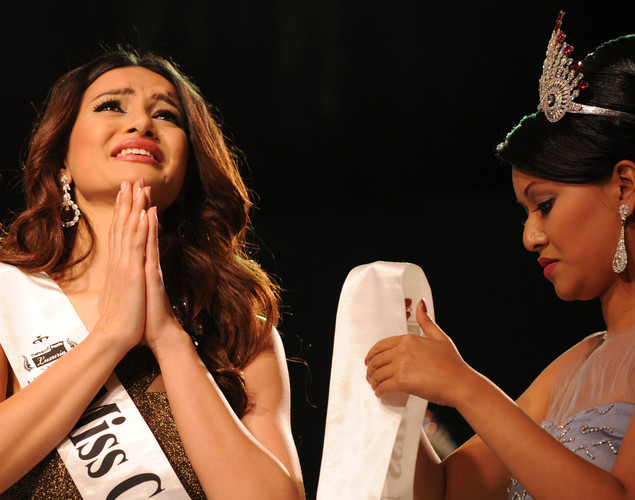 Newly-crowned Miss Nepal Shristi Shrestha (L) gestures while she get crowned following the contest in Kathmandu.