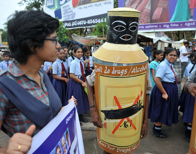 An Indian undergoing alcohol abuse treatment (C) and school children participates in an anti drugs rally for International Day against Drug Abuse and Illicit Trafficking in Warangal.