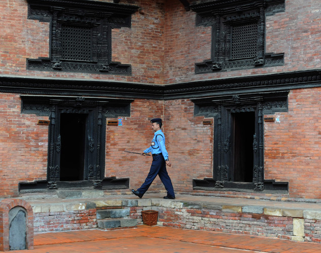 Nepalese police personnel walk pass at Durbar Square in Lalitpur on August 23, 2011. Lalitpur's Durbar Square, a UNESCO World Heritage Site, is best known for its rich cultural heritage, particularly its tradition of arts and crafts.