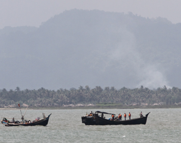 Smoke billows from village houses (background R) believed to be burnt during sectarian violence in Myanmar are seen as boats transporting Rohingya Muslims fleeing sectarian violence attempt to cross the Naf river into Bangladesh in Teknaf.