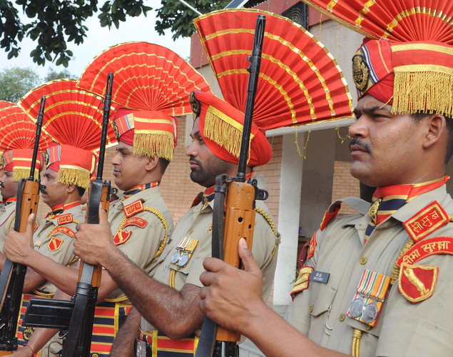 Indian Border Security Force (BSF) soldiers present arms during a ceremony to celebrate India's Independence Day at the India-Pakistan Wagah border post on August 15, 2012.