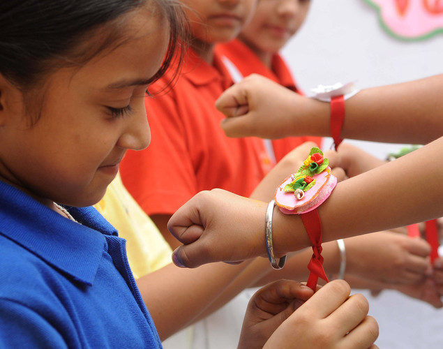 An Indian school girl ties a 'rakhi' (sacred thread) onto the wrist of a school boy on the eve of the Hindu festival Raksha Bandhan at a school in Amritsar.