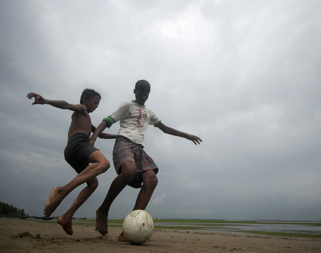 Bangladeshi children play football beside the Naf river in Teknaf on June 14, 2012.