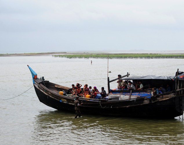 Bangladeshi Border Guards, wading in water, turn back an intercepted boat transporting Rohingya Muslims trying to cross the Naf river into Bangladesh to escape sectarian violence in Myanmar, in Teknaf.